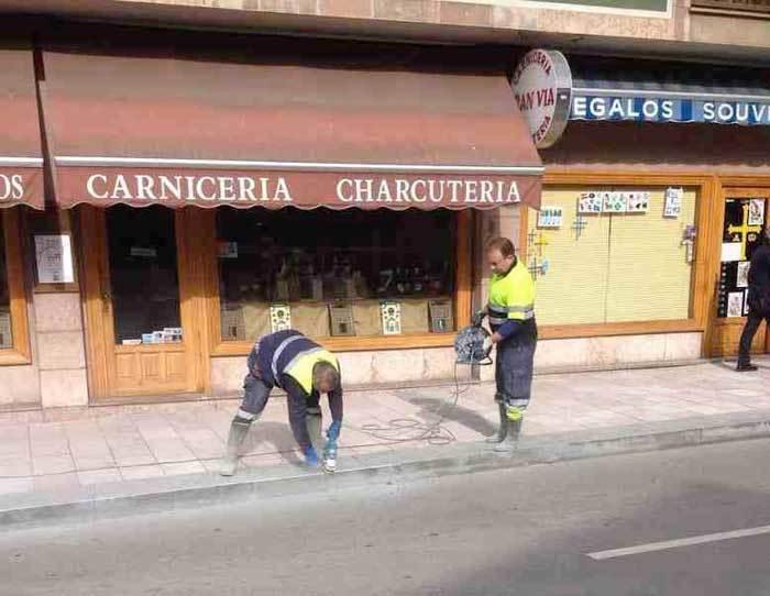 Operarios municipales limando los bordillos de la nueva acera.