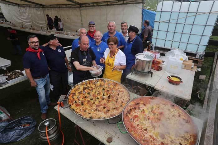 Los cofrades elaborando dos de las cuatro paellas que se cocinaron en Espineres.
