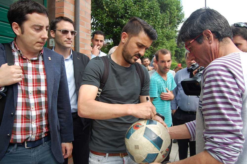 David Villa firmando un balón. Gerardo Sanz, atento.